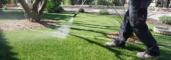 Le nettoyeur haute pression sur une pelouse synthétique